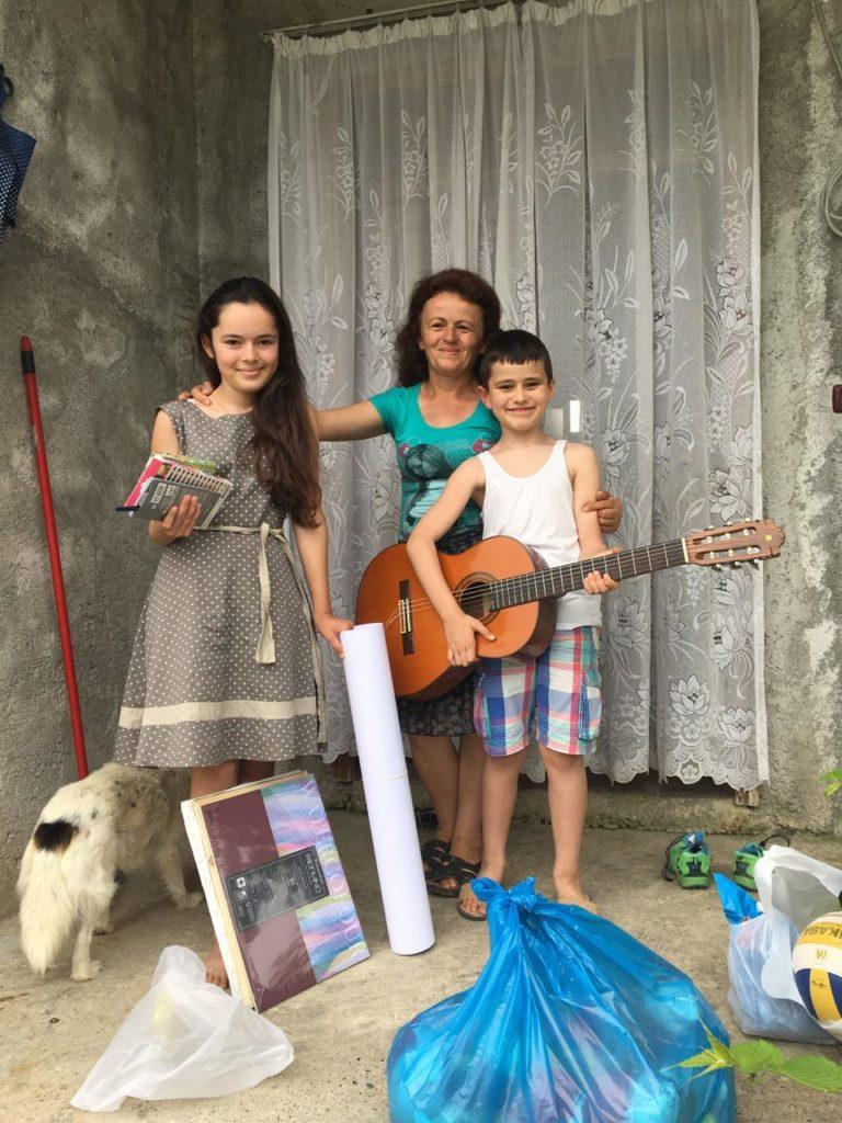 Angela med tegnesakene, Anton med ny gitar og mamma Juste med sekken full av mat. - Takk, Norge, for det vi har fått.